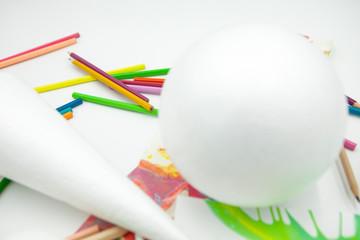 esfera y cono blanco con lápices de colores, pinturas abstractas en fondo blanco