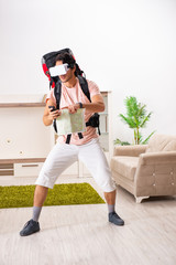 Young male tourist with virtual glasses preparing for trip
