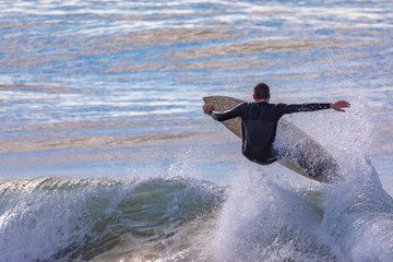 Single Male Surfer airborne over a large wave