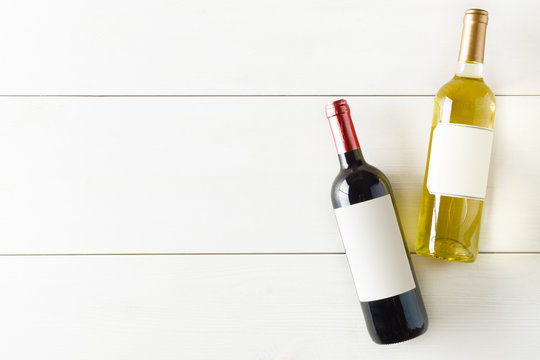 Red and white wine bottle on white wooden table flat lay from above
