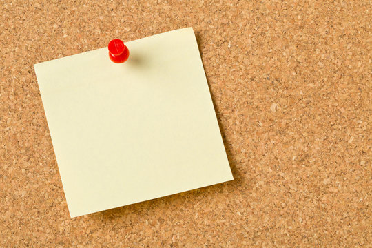 Empty yellow sticky paper memo note with red pin on cork board