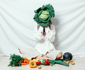 Beautiful caucasian vegan woman with vegetables sitting on a flooor. Spring time concept and healthy meal