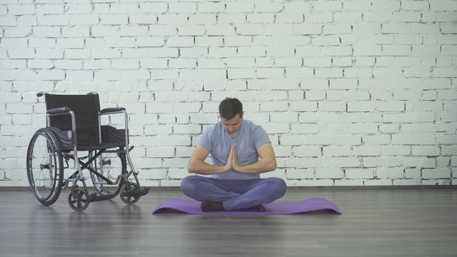 disabled man doing yoga, wheelchair and exercise mat