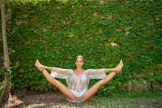 Beautiful, young woman dressed in white romantic blouse practicing yoga in nature. Concept: healthy life, self care, spring resolution, recreation, new beginning, meditation, straddle split, self love