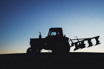 Wall Mural - Tractor on the field. Silhouette against a blue sky