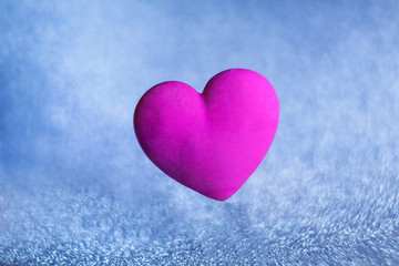 volumetric violet red heart on a blue background of sparkles