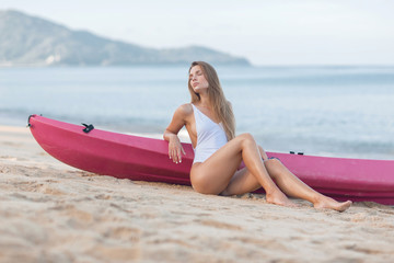 Beautiful girl in a white bathing suit on the ocean shore leans on a kayak