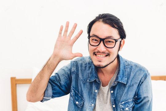 Man smiling at camera waving and saying hello to you