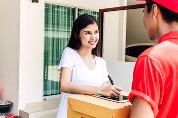 Woman putting signature in tablet on cardboard box to receiving package with delivery man in red uniform.courier service concept