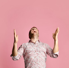 Young happy smiling man in shirt pointing fingers hands up on pink