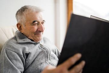 portrait of senior man with family photo album