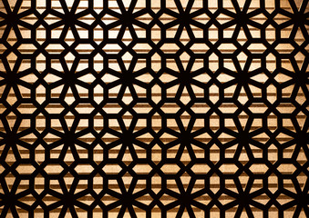 Wooden carve pattern decoration on the wall with lighting in background.