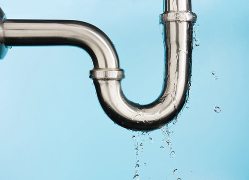 Leaking of water from stainless steel sink pipe on isolated on light blue background