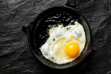 Fond de hotte en verre imprimé Ouf Fried egg on a black cast-iron pan, top view