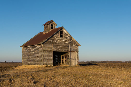Old weathered wooden barn in open field on a Winter afternoon.  LaSalle County, Illinois, USA