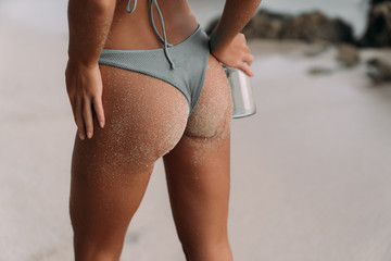 Close-up of tanned booty of female and hand with bottle of clean water on beach with white sand