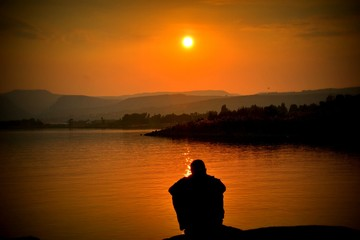 silhouette of woman meditating at sunset