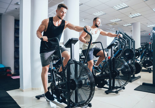 Young men with muscular body using air bike for cardio workout at cross training gym.