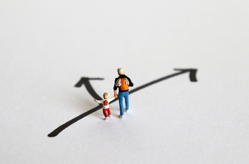 Concept of role conflict. A miniature man and his children standing at a crossroads.