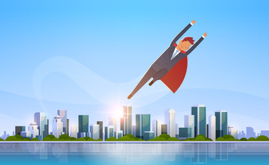 businessman wearing red super hero cape success concept business man flying over big modern city building skyscraper cityscape skyline flat horizontal