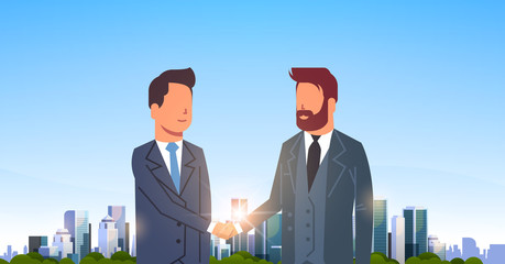 two businessmen shaking hands partners successful agreement business deal hand shake concept over big modern city building skyscraper cityscape skyline flat horizontal