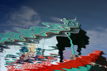 Abstract reflection in water of a colorful wooden fishing boat