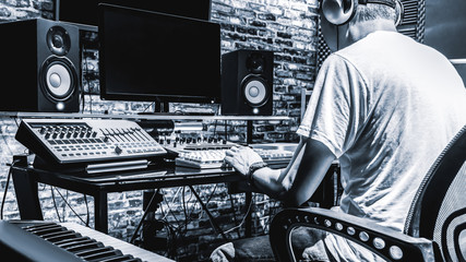 back of male DJ, producer, composer, sound engineer, editor working in sound studio, broadcasting studio, home studio for post production