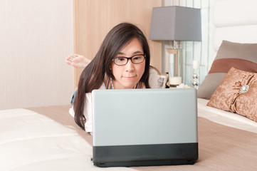 Portrait of young asian beautiful girl wearing eyeglass while laying down on bed with computer.  modern lifestyle concept.