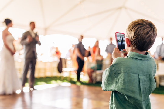 young boy holding a smart phone taking a picture of a bride and groom on their wedding day