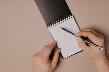 Hand writing in notepad using a pencil, on gray background