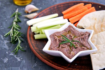Red bean dip with baked garlic, thyme and olive oil in a star bowl. Served with chopped raw carrots, celery and pita pieces.