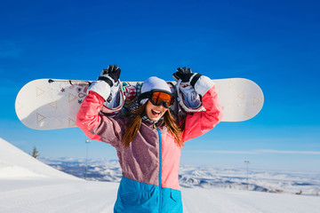 happy cheerful woman in a ski suit and glasses holds a snowboard in her hands in winter. Extreme