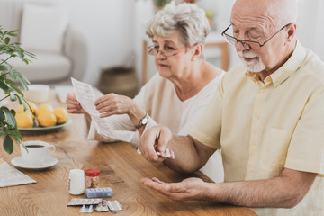 Senior couple sitting at the table and taking medicines
