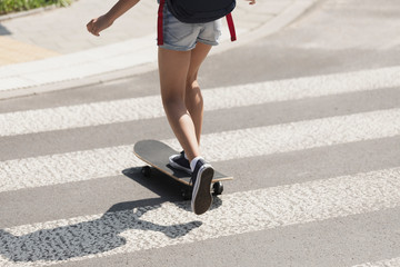 Girl crossing a street on a skateboard