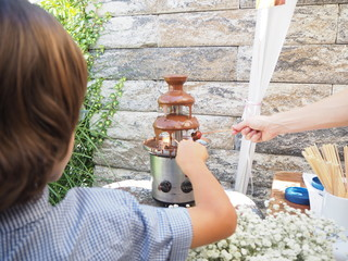 Kids are holding a strawberry stick to dip into a chocolate fountain on children's birthday party.