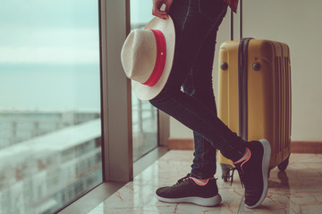 Young woman traveler in casual clothes with a yellow suitcase and a traveler's hat in hands going on vacation.