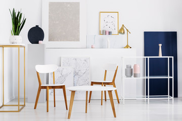 White chairs at wooden table in simple apartment interior with plant, posters and gold lamp. Real photo