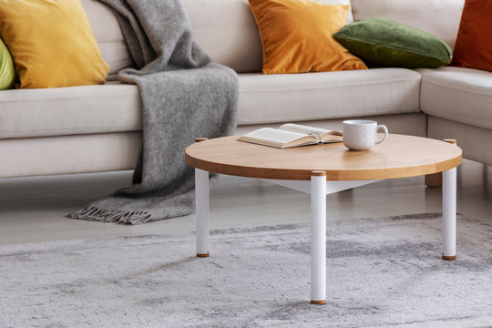 Round wooden table with book and cup on grey carpet next to sofa in flat interior. Real photo