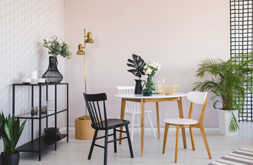 White and black chair at wooden table with plant in dining room interior with gold lamp. Real photo