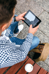 Top view of unrecognizable young man using tablet outdoors