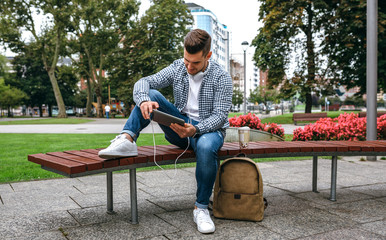 Young man using tablet sitting on a park bench outdoors