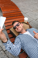 Young man lying on a park bench making a selfie with the mobile