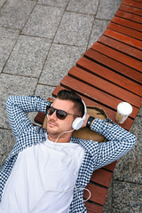 Young man with headphones lying on a park bench outdoors