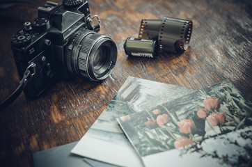 Retro photo camera, film and old photos on the table