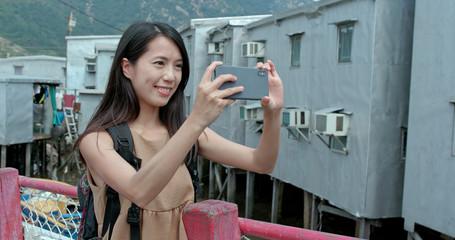 Woman take photo on cellphone in Tai O village