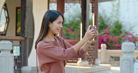 Woman take photo on cellphone in chinese garden