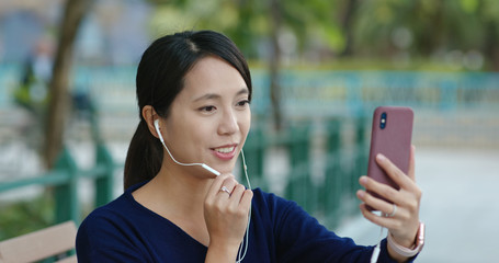 Woman make a video call on cellphone in the park