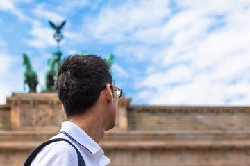 Berlin Landmark Tourist View Background / Young asian tourist or business man in Berlin (Germany) looking up to statue of Brandenburg Gate (copy space)