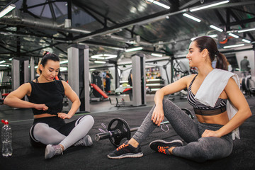 Picture of two young women sitting on floor in gym. Asian model tie knot on shirt and look down. Young european woman look at er and hold white towel on shoulder.