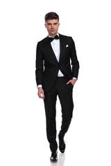 relaxed groom in black tuxedo walks forward